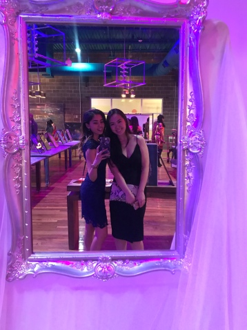 two women take a photo in front of mirror