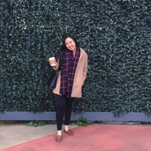 Woman in winter clothing posing in front of a green wall at the Dallas Farmers Market