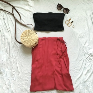 Black swim top with red skirt and circle straw bag