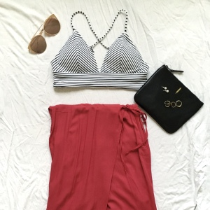 Striped swimsuit top with red skirt and black bag
