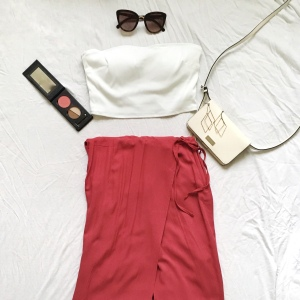 White swimsuit tube top with a red skirt and a white purse with other accessories around the outfit