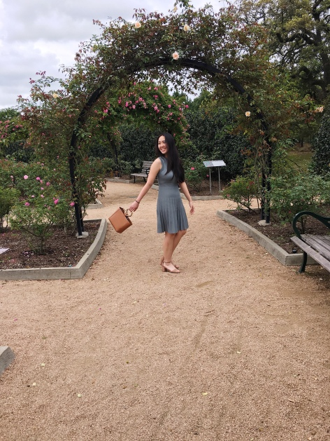 woman under rose arch wearing a sage dress while swinging a brown bag