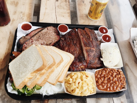 Meal tray from Corkscrew BBQ with brisket, ribs, bread, and sides