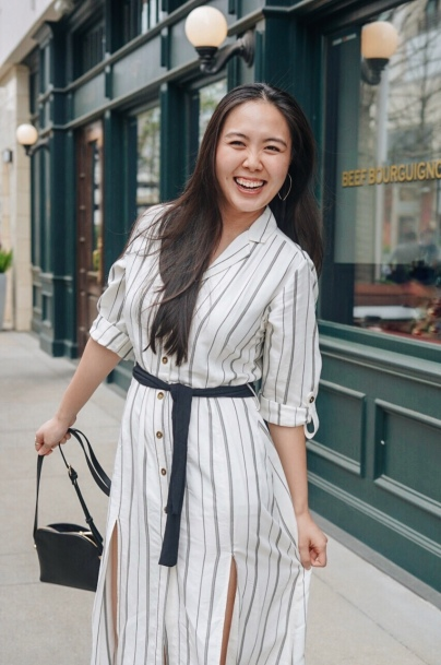 woman in white striped button up dress holding a black bag