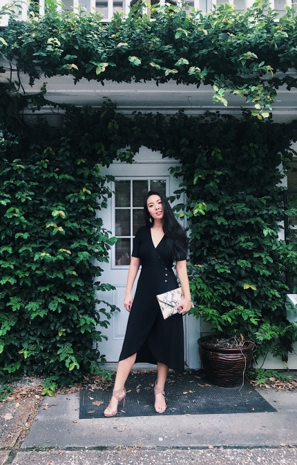 woman in black dress with faux reptile clutch