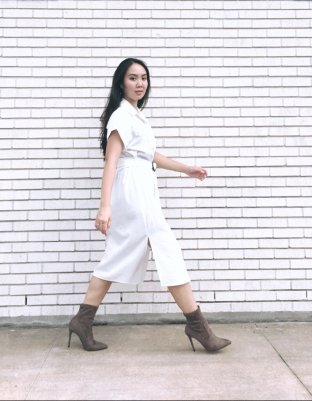 Woman walking in taupe booties and wearing a white dress