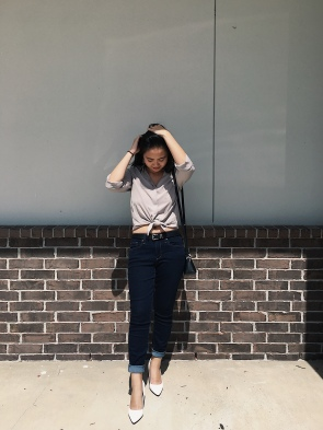 Woman posing in a taupe button up, jeans, and white heels